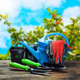 Garden tools lying on a wooden table. On a landscape Royalty Free Stock Photo