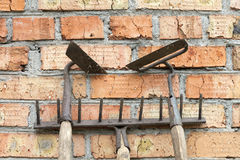 Garden tools: old and rusty rakes and hoes against the old weathered brick wall royalty free stock photo