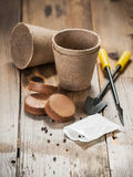 Garden tools, peat pots and seeds on wooden background Royalty Free Stock Photos