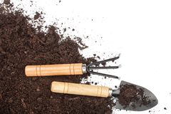 Garden tools in soil isolated on white background with copy space for your text. Top view Royalty Free Stock Photos
