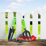 Garden tools and a white fence Royalty Free Stock Image