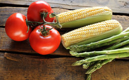 Garden Vegetables. Fresh garden vegetables of corn, tomatoes and asparagus isolated on wood background Stock Photos