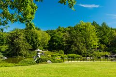 Garden View on Bright Day. Bright view of a garden on a clear blue day. Lush green vegetation in a field with trees and grass Asian or oriental shrine or garden stock images