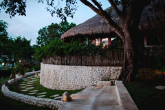 Garden and villa at dusk. View of the garden and a stone villa with a thatched roof in the twilight stock image