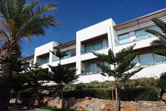 Garden with villas. HERAKLION, CRETE, GREECE - MAY 13, 2014: The blue sky, modern building of villa with balcones and palms on the terrain of luxury class hotel Stock Photography