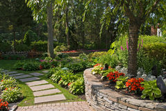 Garden Wall. A Summer view of an ornamental garden with a slate pathway and garden wall Royalty Free Stock Image