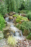 Garden Water Feature. A man-made waterfall feature surrounded by lush foliage in a landscaped garden Royalty Free Stock Photography