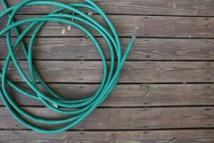 Garden Water Hose Coiled up On Old Wood Deck royalty free stock image