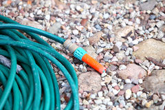 Garden water hose outdoor sand Royalty Free Stock Photos