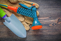Garden water pistol safety gloves hand spade on wooden board gar Stock Images