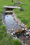 Garden water  stream. Stream of water in  a spring garden Royalty Free Stock Photos