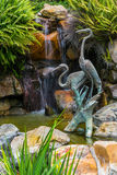 Garden Waterfall. Heron sculptures in front of a garden waterfall Stock Images