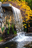 Garden waterfall pond autumn fall leaves. Waterfall feature in garden with pond, stone wall and autumn fall leaves Stock Photo