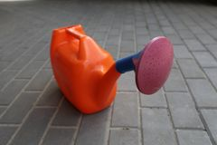 Garden watering can of orange color with a claret tip costs on a tile royalty free stock photo