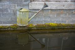 Garden Watering Can Reflected in Water. Vintage Metal Garden Watering Can with moss stains reflected in water of water trough at a nursery royalty free stock images