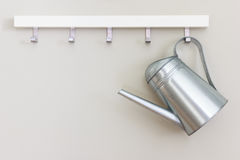 Garden watering pot. Metal garden watering pot hanging on the wall Stock Photography