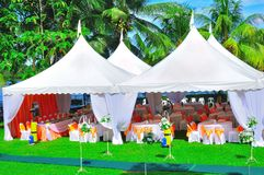 Garden wedding and party. The view of the tents and bouquet in a tropical garden, nicely decorated for wedding reception or garden party Royalty Free Stock Photo