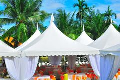 Garden wedding and party. The view of the tents and bouquet in a tropical garden, nicely decorated for wedding reception or garden party Stock Images