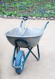 Garden wheelbarrow with blue wheel and gardening tools inside Stock Photo