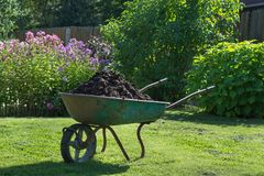 Garden-wheelbarrow filled with soil on a farm. Stock Photography