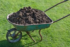 Garden-wheelbarrow filled with soil on a farm. Outdoors Stock Images