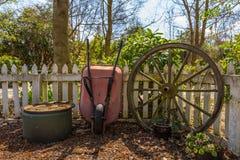 Garden wheelbarrow and and old bullock cart wheel Royalty Free Stock Photos
