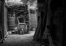 Garden wheelbarrow And Rainwater Tank Near Barn Stock Images