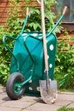 Garden wheelbarrow and shovel in village yard Stock Photos