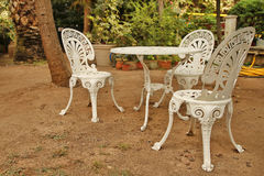 Garden white furniture. Metal garden white furniture in the middle of the garden Stock Photo