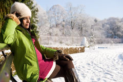 Garden winter. A pregnant woman in thought on a bench in a garden in winter Royalty Free Stock Photo