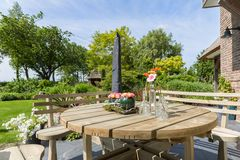 Garden with wooden bench and table. Garden terrace with wooden bench and table Royalty Free Stock Images