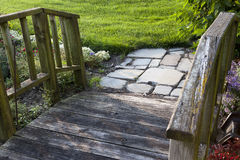 Garden wooden pathway with stone pavers. A wooden garden bridge with stone pavers Royalty Free Stock Photography