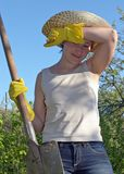 Garden work. Tired woman with shovel mopping sweat from her brow Stock Images