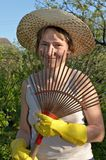 Garden work. Portrait of smiling woman with fan royalty free stock photos