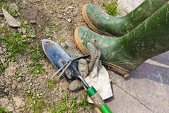 Garden works. Some tools and a pair of boots just used for some works in the garden Royalty Free Stock Images