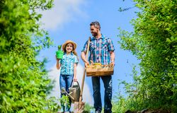 Garden works. Spring garden. Spring gardening checklist. Father and daughter with shovel and watering can in garden. It stock image
