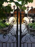 Garden: wrought iron courtyard gates. Black wrought iron gates to sunny courtyard garden Royalty Free Stock Image