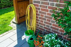 A garden yellow hose connected to a tap protruding from a farm building against a background of brick facade, a photo closeup. stock images