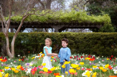 Garden of Youth 2. Two young friends a boy and a girl stand amongst blooming flowers in a beautiful garden Royalty Free Stock Images