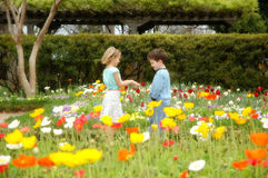 Garden of youth. Young girl offers her hands to a young boy amongst a brightly colorful garden of flowers Stock Images