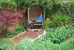 Gardener. Tired gardener sitting on the bench and relaxing Royalty Free Stock Image