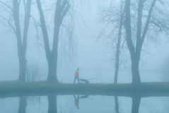 Gardener. The gardener on coast of lake. Earlier morning. A fog Royalty Free Stock Photography