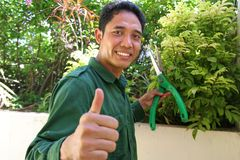Gardener. Showing tumb up with smile at work. this series here stock photos