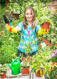 Gardener active happy girl is holding the pot of flower and gard Royalty Free Stock Images