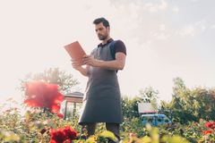 Gardener in apron using tablet while working in garden. Low angle view of gardener in apron using tablet while working in garden Stock Photography