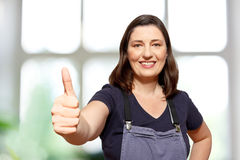Gardener bib overall thumb up. Middle aged female gardener  or saleswoman in DIY store in bib overall showing the thumbs up sign, blurry white and green Stock Photos