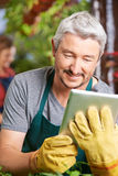 Gardener buying plants with tablet computer. Gardener in a greenhouse buying new plants with a tablet computer Stock Images