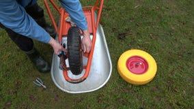 Gardener changing and fixing wheelbarrow wheel. Gardener farmer changing and fixing wheelbarrow wheel stock video