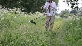 Gardener cut grass. Gardener man take trimmer cut tool and start cut wet grass stock video footage