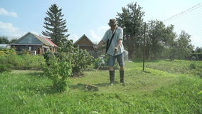Gardener cuts the grass with a lawnmower outdoors. The gardener cuts the grass with a lawnmower outdoors in sunny day stock footage